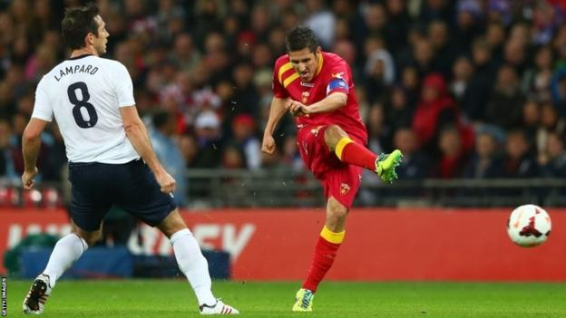 Stevan Jovetic of Montenegro takes a shot as Frank Lampard of England looks on during the 2014 World Cup qualifying match