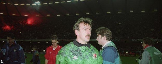 Neville Southall is dejected after his side's defeat by Romania