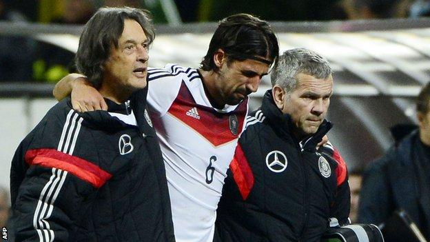 Germany and Real Madrid midfielder Sami Khedira is helped off the pitch after tearing a cruciate ligament while playing for his country against Italy