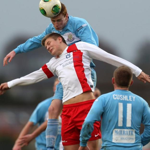 Ballymena United's Aaron Stewart jumps to win an aerial battle against Andrew Mitchell of Ards