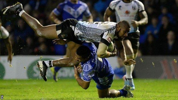 Fiji's Marika Koroibe is tackled by Samoa's Anthony Milford