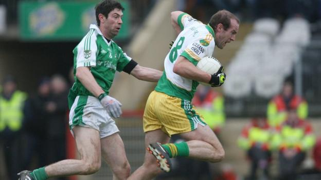 Roslea's Kevin Cosgrove closes in on Glenswilly midfielder Neil Gallagher at Healy Park