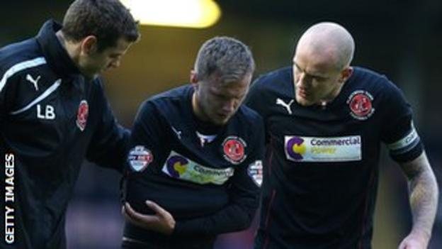 Fleetwood striker David Ball is helped off the field at Northampton