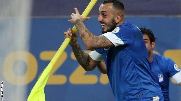 Konstantinos Mitroglou celebrates with the corner flag after putting Greece ahead