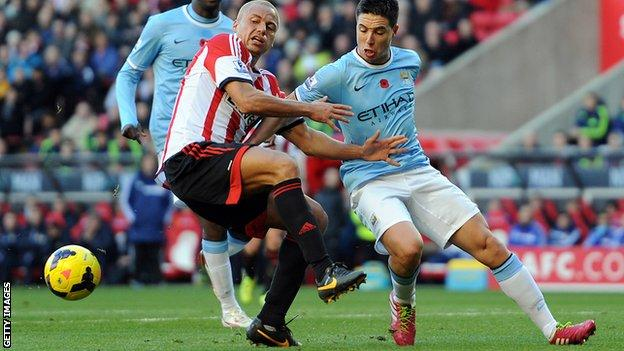 Wes Brown (left) of Sunderland in action with Samir Nasri of Manchester City