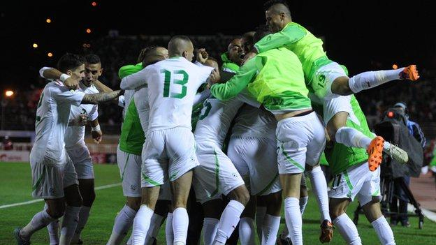 Algerian players celebrate winning their World Cup play-off against Burkina Faso