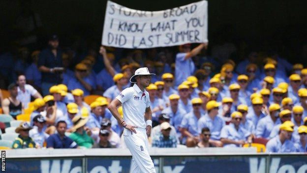 Stuart Broad fields while Australian fans hold up a banner behind him