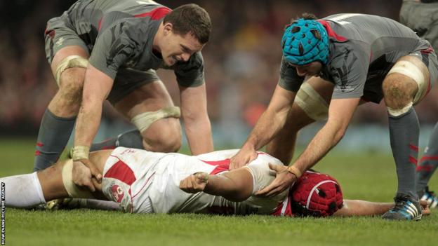 Ian Evans and Justin Tipuric tend to a stricken Sione Kalamafoni after the Tongan suffers a bow to the head in a tackle