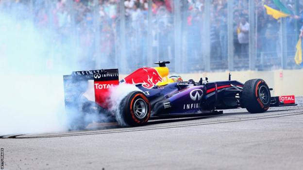 Sebastian Vettel performs donuts in his car after winning the Brazilian GP