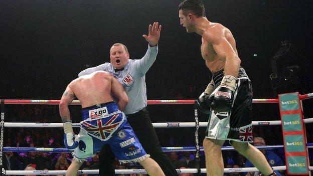 George Groves is held by referee Howard Foster as Carl Froch looks on