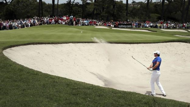 Northern Ireland's Rory McIlroy plays a bunker shot on the first hole - starting the final day of the Australian Open four shots behind home favourite Adam Scott