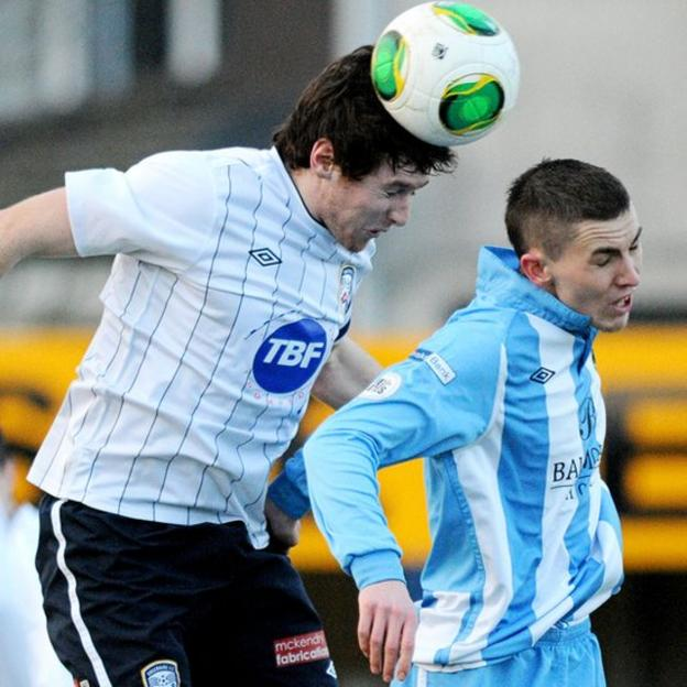 Howard Beverland wins a high ball against Warrenpoint's Daniel Hughes at Stangmore Park