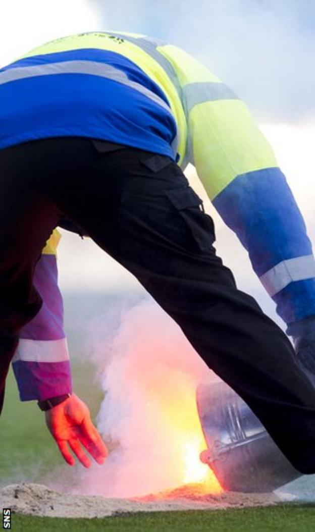 A Falkirk steward douses the flames of a flare on the pitch on Saturday