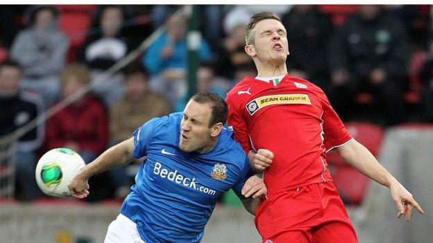 Guy Bates and Jaimie McGovern in aerial action during the Premiership game between Cliftonville and Glenavon