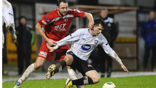 Portadown midfielder Tim Mouncey sends Coleraine's Gareth Tommons crashing to the ground at Shamrock Park