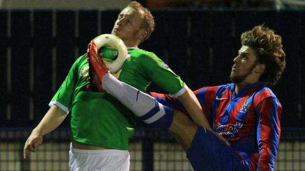 Cliftonville striker Liam Boyce is challenged by Steven McCullough of Ards during the match at Clandeboye Park