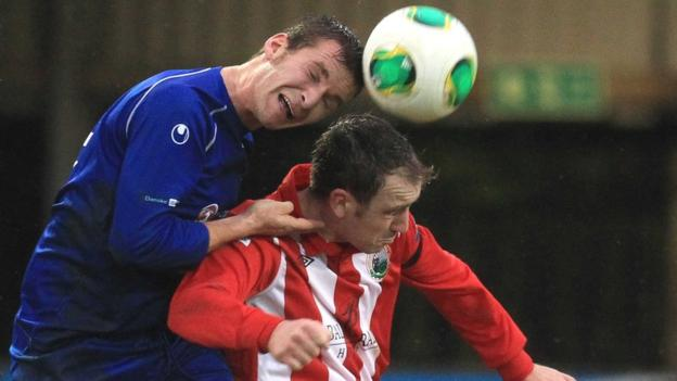 Dungannon's Johnny Topley gets above Warrenpoint Town opponent Padraig Smith at Stangmore Park