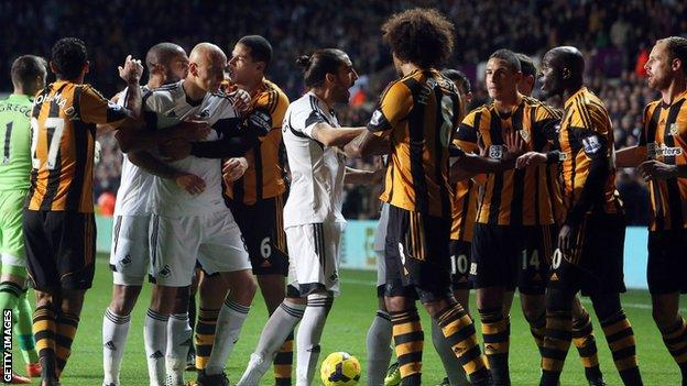 Players clash during Swansea City v Hull City match