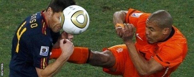 Nigel de Jong tackles Xabi Alonso