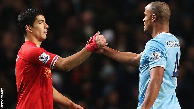 Liverpool's Luis Suarez shakes hands with Man City's Vincent Kompany