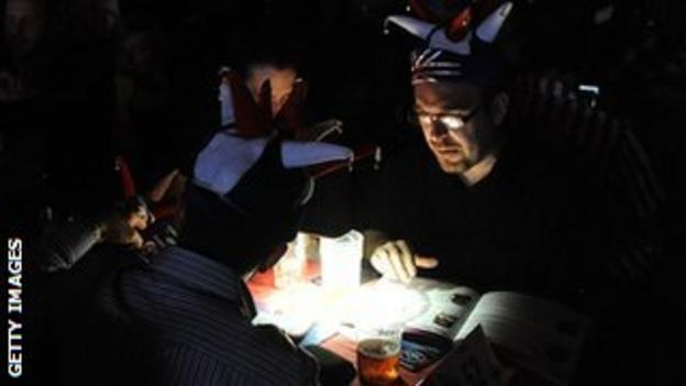 Spectators use their phones to read programmes during the Lakeside power cut