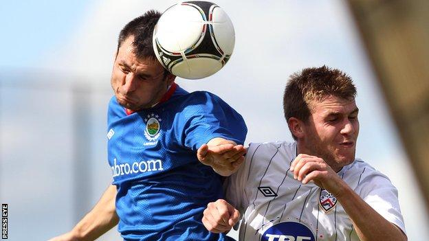 Jim Ervin beats Coleraine's Stephen Lowry to the high ball