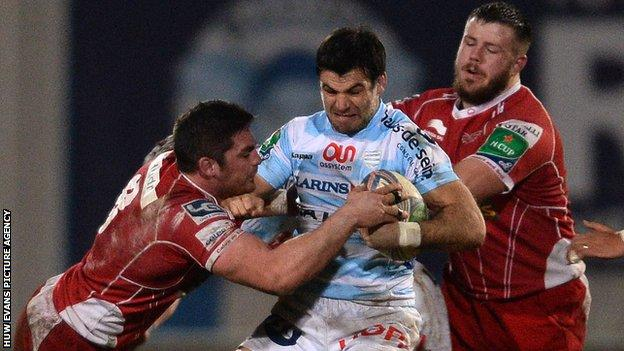Mike Phillips of Racing Metro is tackled by Rob McCusker of Scarlets