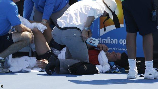 Frank Dancevic of Canada lies on the court after collapsing during his first round match against Benoit Paire of France