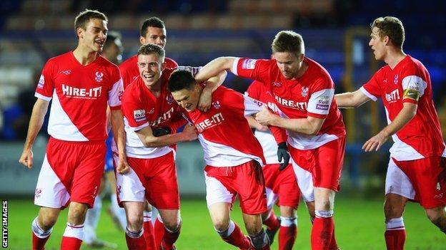 Joe Lolley celebrates Kidderminster's winner at Peterborough with team-mates.