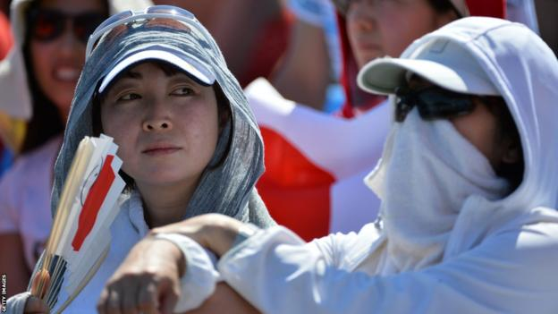 Spectators cover up to beat the heat as they watch Japan's Kei Nishikori