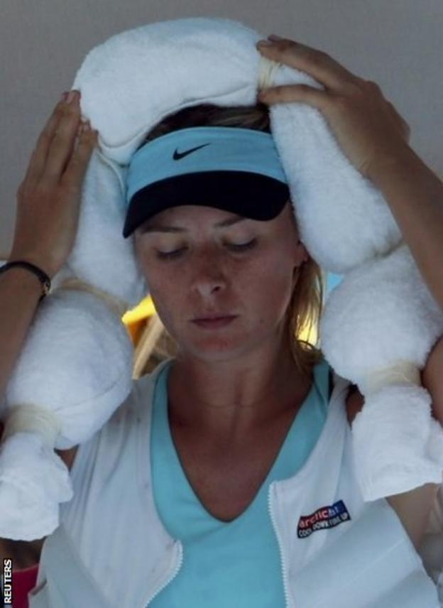 Maria Sharapova of Russia holds an ice-packed towel to her head while wearing an ice vest