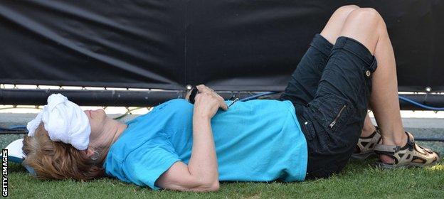 A tennis fan seeks the shade as temperatures remain high