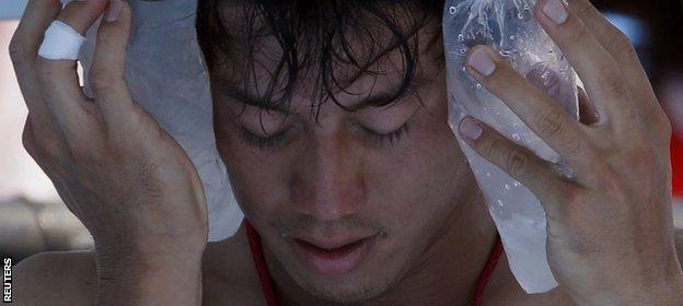 Japan's Kei Nishikori holds an ice pack to his face during his match against Dusan Lajovic of Serbia