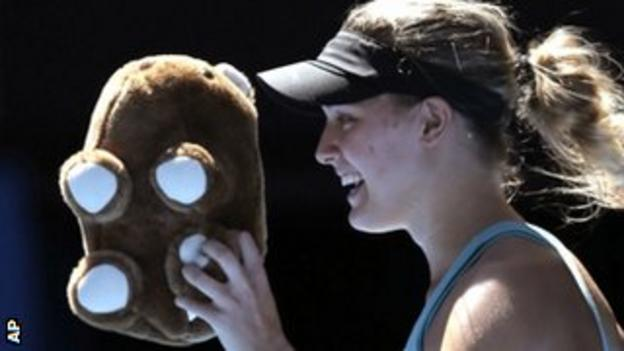 Eugenie Bouchard walks off the court with a toy wombat thrown to her by a supporter
