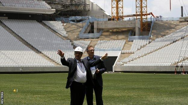 Jerome Valcke (right) speaks with an engineer during a visit to the Arena Corinthians stadium