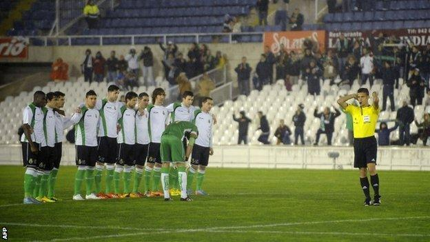 Racing Santander players watch on as the game against Real Sociedad is called off