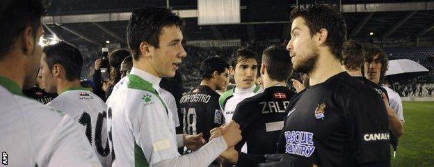 Racing Santander defender Saul Garcia speaks with Real Sociedad defender Inigo Martinez