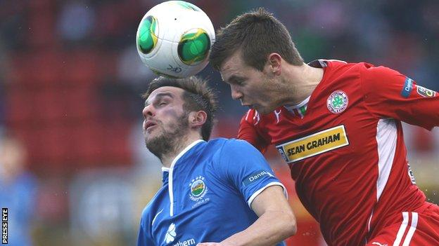 Linfield's Andy Waterworth is beaten to the high ball by Jaimie McGovern