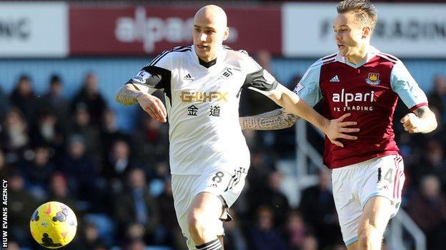 Swansea's Jonjo Shelvey takes on West Ham's Matt Taylor