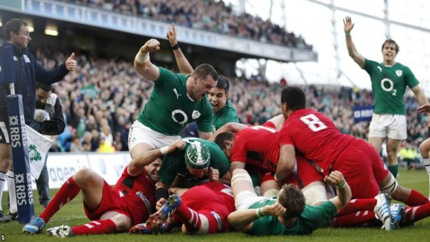 Ireland celebrate as flanker Chris Henry goes over for the game's opening try