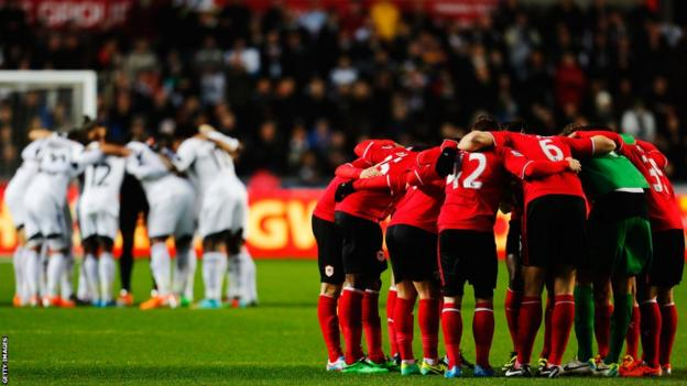The Swansea players and their Cardiff rivals (foreground) go into a huddle before kick-off