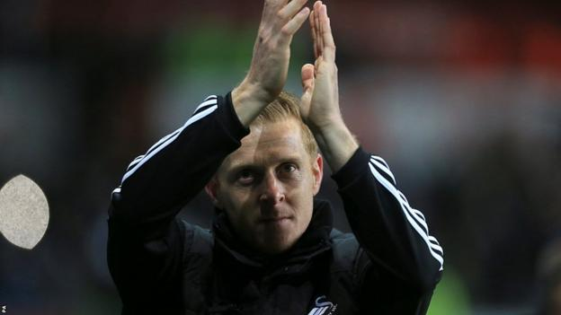 Garry Monk applauds the Swansea fans at the Liberty Stadium after the caretaker boss leads them to victory over Cardiff in his first game in charge