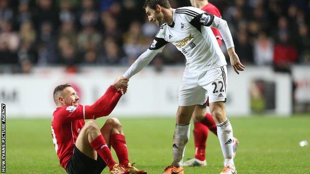 Cardiff's Craig Bellamy and Angel Rangel of Swansea share a more light-hearted moment during the south Wales derby
