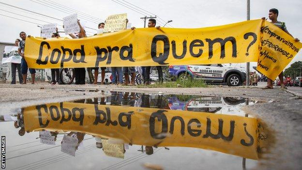 """Protestors outside the Amazonia Arena with a banner that reads """"World Cup for whom?"""""""