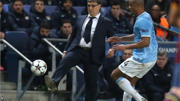 Barcelona head coach Gerardo Martino beats Manchester City defender Vincent Kompany to the ball