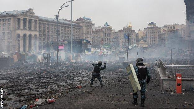Berkut riot police throw stones at anti-government protesters, who are throwing rocks in return, on Independence Square on February 19, 2014 in Kiev, Ukraine
