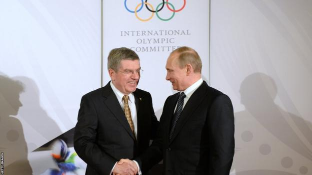SOCHI, RUSSIA - FEBRUARY 06: President of the International Olympic Committee (IOC), Thomas Bach (L) shakes hands with Russian President Vladimir Putin before the IOC Gala Dinner on the eve of the Sochi 2014 Winter Olympics on February 6, 2014 in Sochi, Russia.