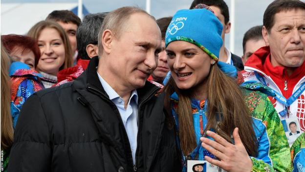 Russian President Vladimir Putin (left) listens to Russian pole vault champion and Olympic village mayor Yelena Isinbayeva at the Olympic village in Sochi on February 5, 2014, two days ahead of the opening ceremony.