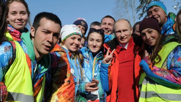 Russia's President Vladimir Putin poses for a photo with volunteers during the men's cross-country 4 x 10 km relay event at the 2014 Sochi Winter Olympics on February 16, 2014.