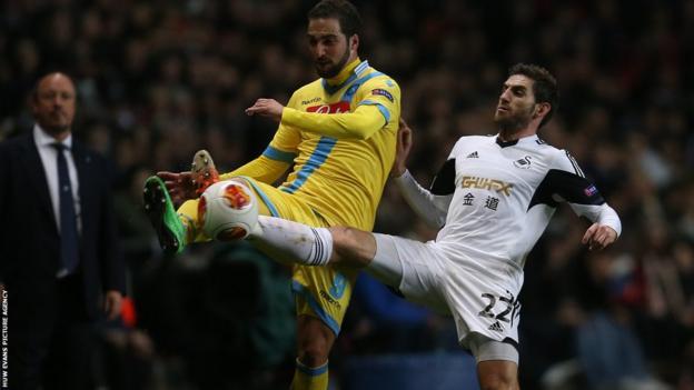 Swansea full-back Angel Rangel battles for the ball with striker Gonzalo Higuain under the watchful gaze of Napoli coach Rafa Benitez.
